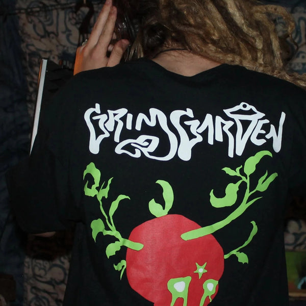 Black Tshirt on Grunge Vocalist in Dark Room Back of Shirt Grim Garden across the top from shoulderblade to shoulderblade in White Plastisol Ink below that a red skull with bleeding oozing green out of eyes and three plants growing out of the top of the skull resembling jersey tomato