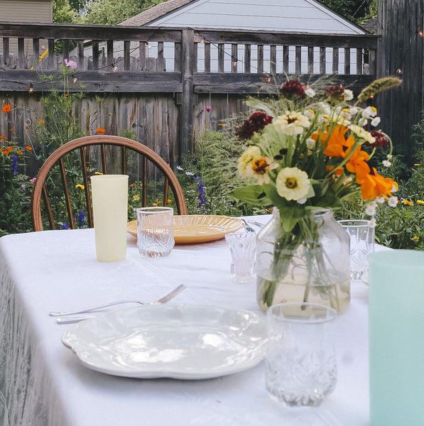 Garden dinner party, outdoor table with white table cloth in a wild flower garden