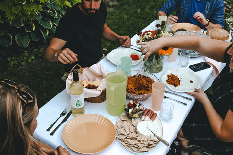 People gathered around a table eating dinner outside