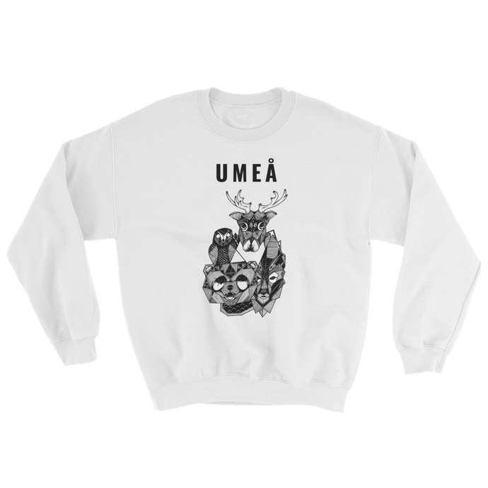 White sweater with the Umeå design of a reindeer, an owl, a bear and a wolf gathered around Nydala lake. Original artwork by Jonn Designs.