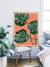 Load image into Gallery viewer, Monstera Orange Botanical Illustration Print sitting on a chair in a bedroom