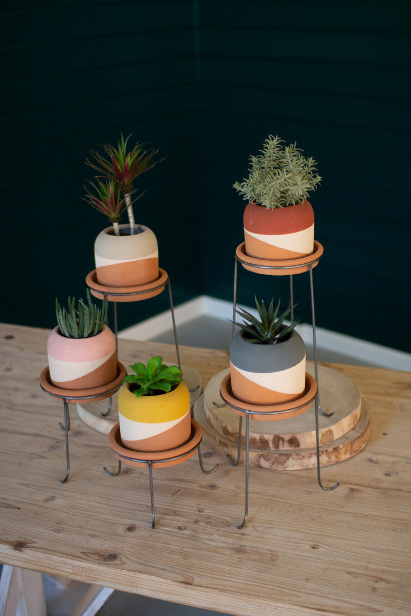 Set of five color dipped clay pots with metal bases