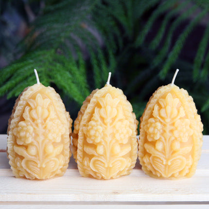 A trio of decorative beeswax egg candles
