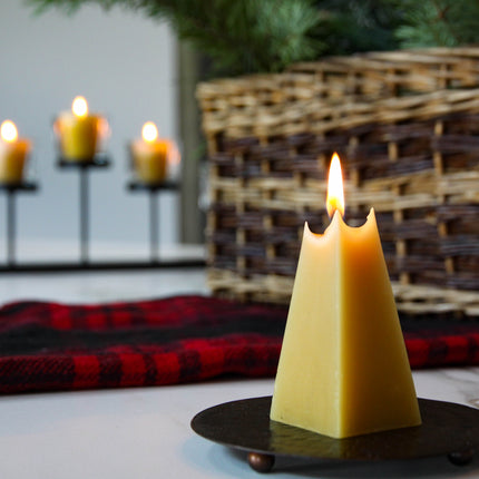 burning candle shaped like a pyramid with beeswax candles in background