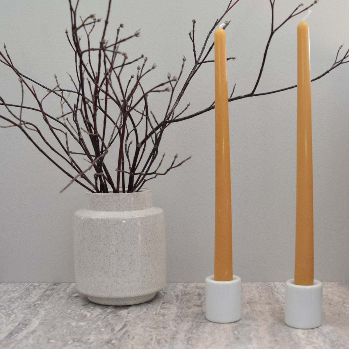 Pack of two taper pair beeswax candlesticks in simple white candlestick holders