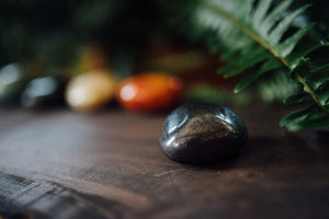 Hematite, one of seven polished palm-sized precious stones for chakra healing and crystal healing designed to support the Root Chakra