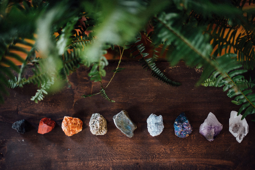 Nine raw precious stones for chakra healing and crystal healing including black tourmaline, red jasper, orange calcite, pyrite, celestite, bornite, amtheyst, and clear quartz