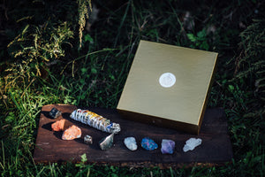 Chakra box for chakra healing and crystal healing featuring precious stones, essential oils, precious stones, ceremonial cacao, and an herbal bundle
