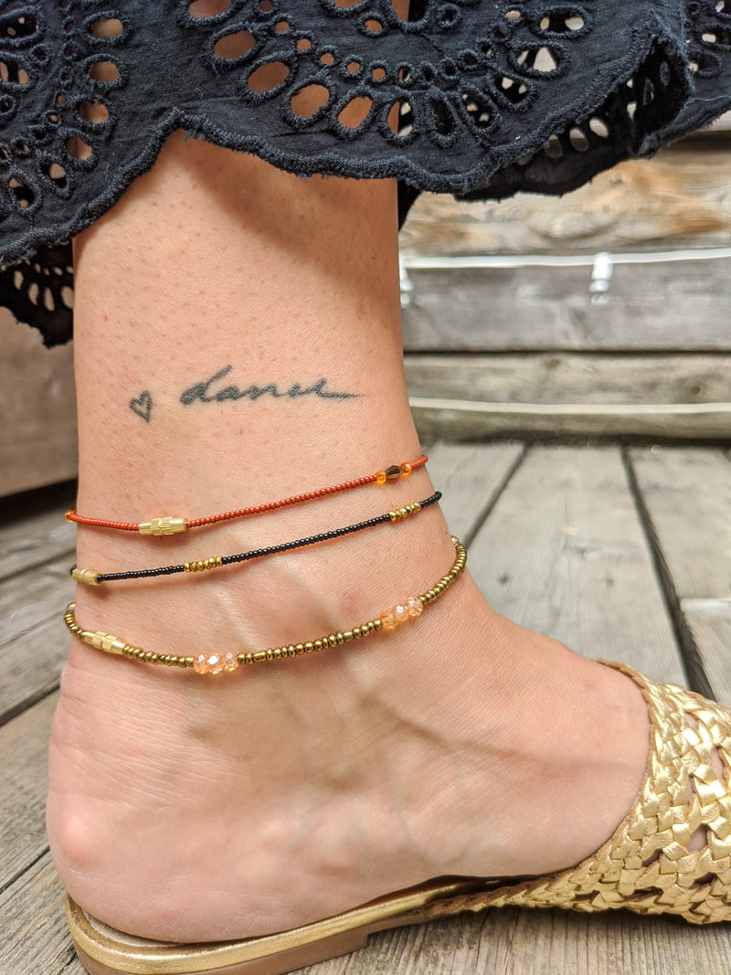 Red, Black, and Brass Anklet Stack