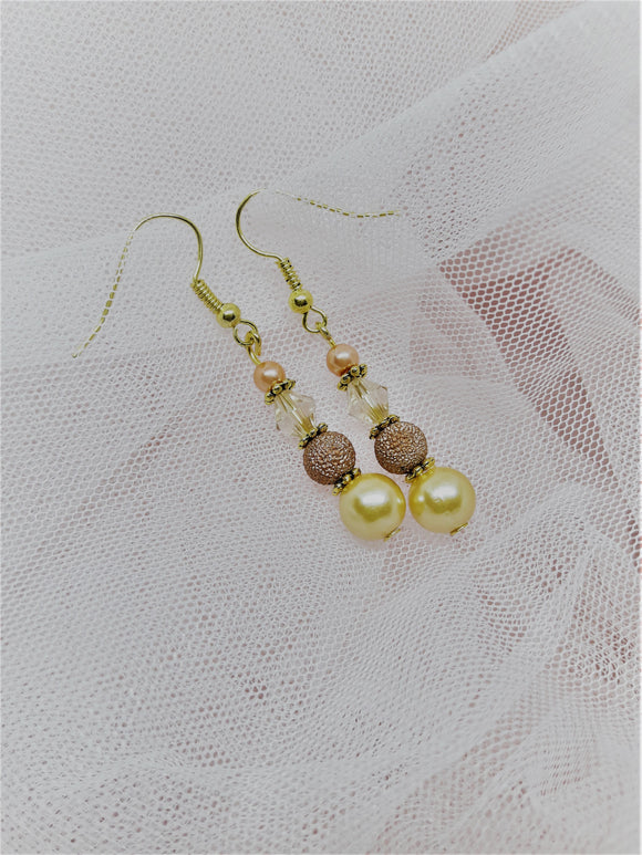 Gold earrings with peach tones