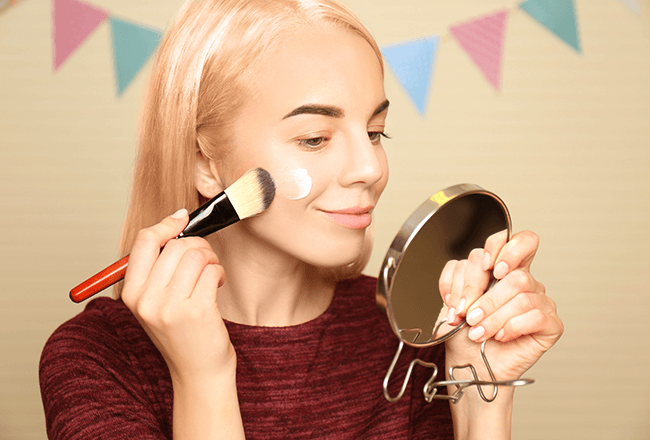 woman applying makeup primer