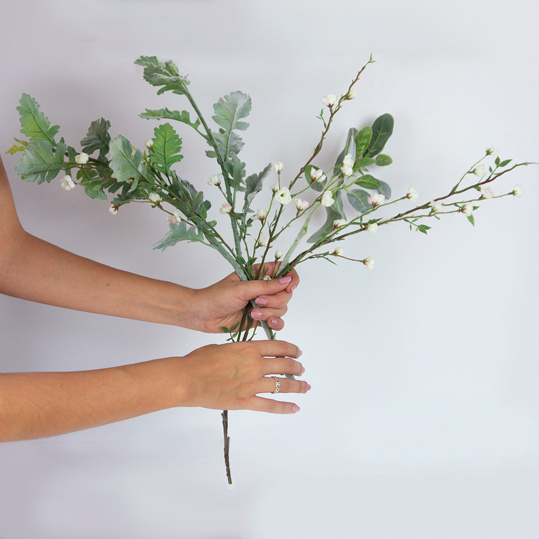 Arrange foliage and greenery stems in an X shape