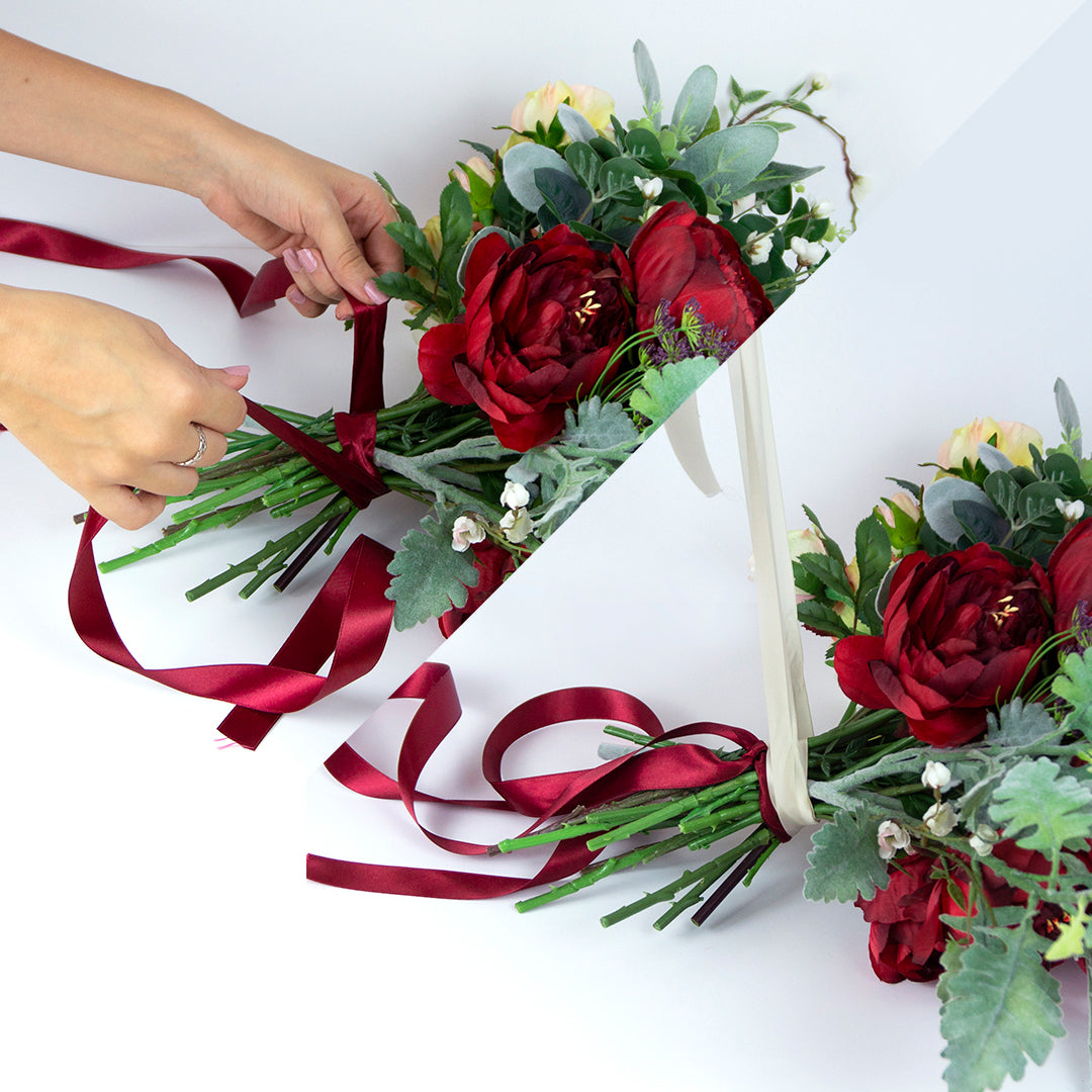 Wrapping a bouquet with two silk ribbons, bridal and burgundy colour