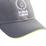 Grey baseball hat with green trimming and white embroidered logo