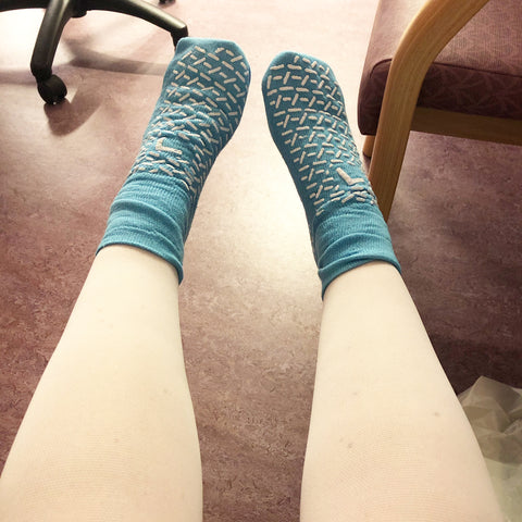 Pair of legs in white surgical stockings with lightblie comfort socks pre-surgery for Endometriosis