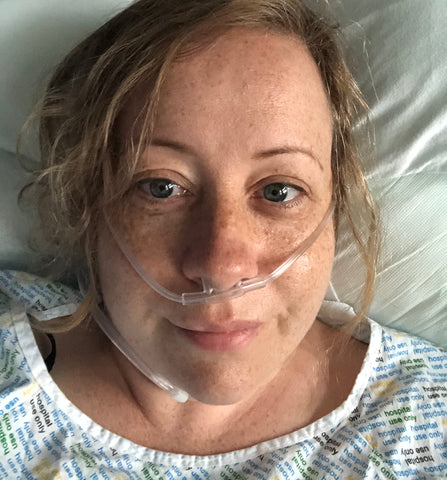 Mhairi, white female, lies in bed on oxygen after Endometriosis operation