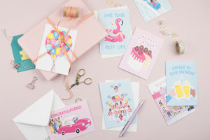 A flat lay image of birthday cards printed in the UK featuring birthday cheerleaders, birthday cakes and flamingo pool floats
