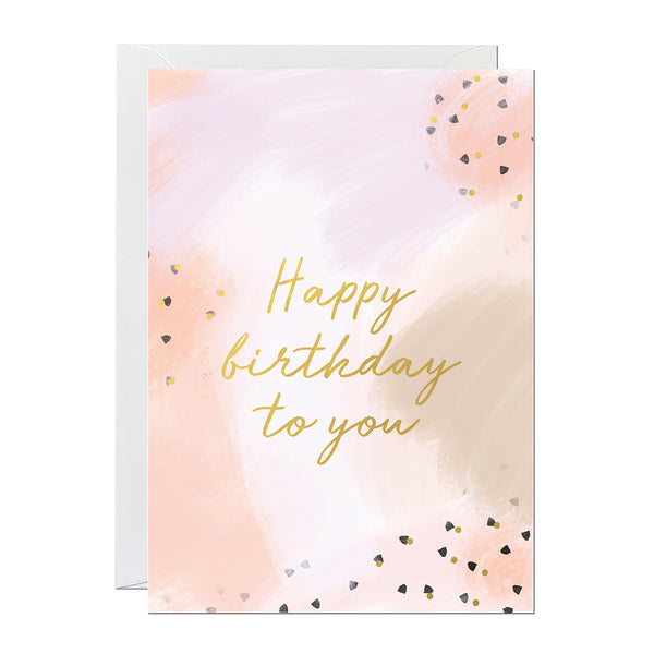 A birthday card with gold foiled lettering reading 'happy birthday to you' printed on a hand-painted canvas background.