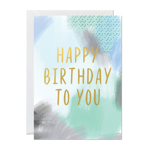 A birthday card perfect for men with a green and blue painted canvas background and a gold foil greeting reading 'happy birthday to you'