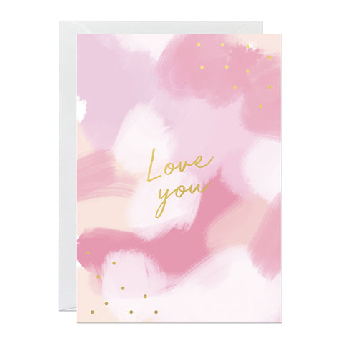 A Valentine's Day card that features a hand-painted pink canvas and a gold foil lettered greeting that reads 'love you'