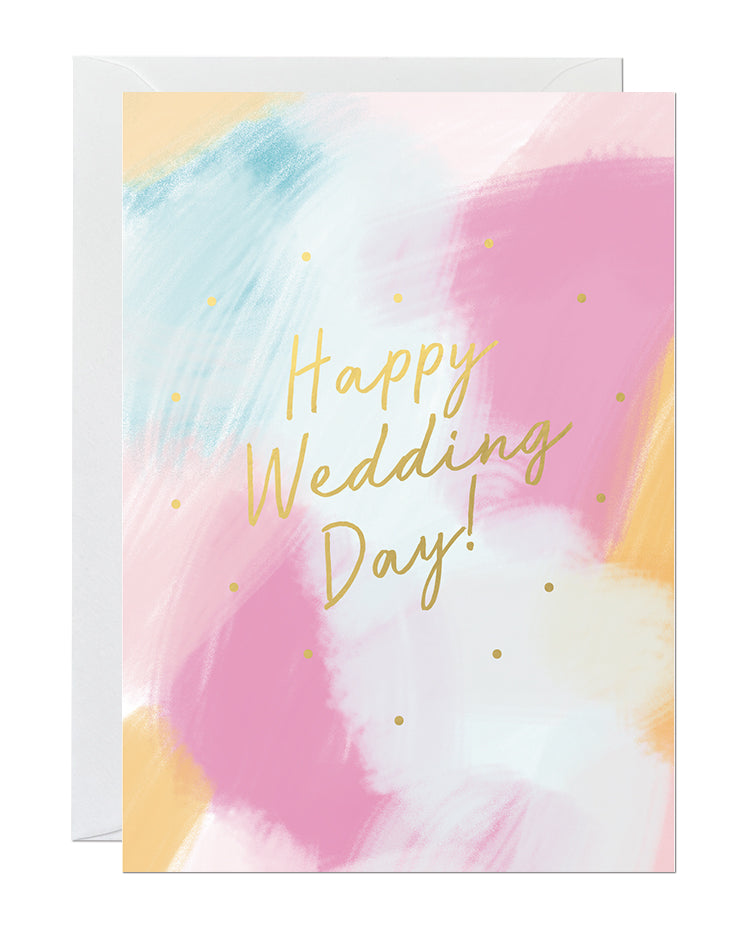 A wedding card featuring a hand-painted canvas background and gold foil lettering that says 'happy wedding day'