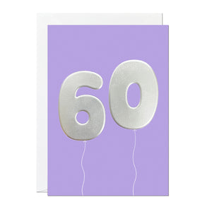 A 60th birthday card featuring big helium balloons printed with an embossed silver foil on a purple card.