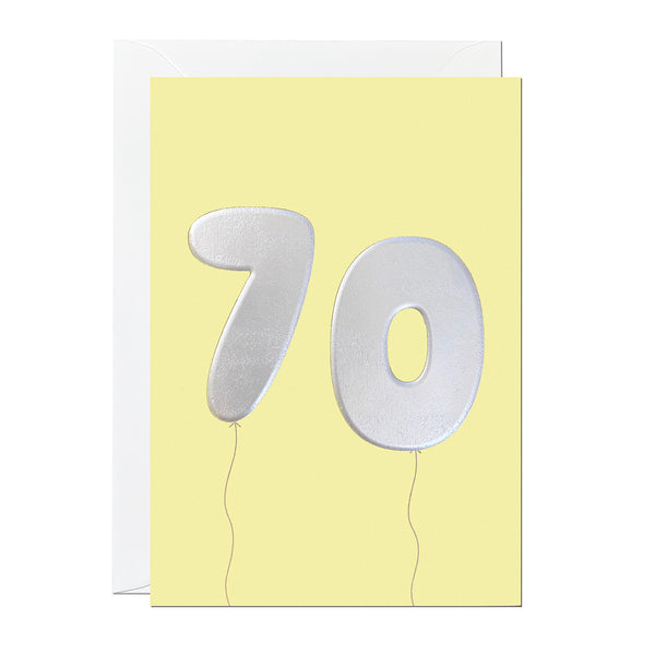 A yellow 70th birthday card featuring birthday balloons that have been printed with an embossed silver foil