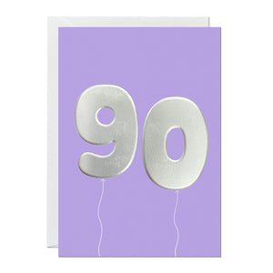 A 90th birthday card featuring big helium balloons printed with an embossed silver foil on a purple card.