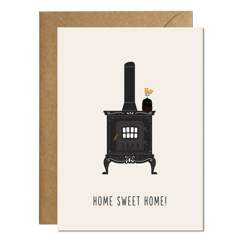 A new home card featuring an illustration of a log burner and a greeting that reads 'home sweet home'