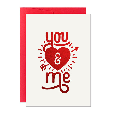This is a Valentine's Day card that has a hand-lettered greeting that reads 'You and Me' with a cupid-inspired heart and arrow, printed with a sparkly red foil in the UK, paired with a red envelope.