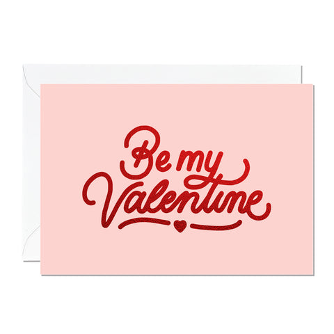 This is a Valentine's Day card that says 'Be My Valentine'. It's printed with a light pink background and features hand lettering printed with a luxury sparkly red foil