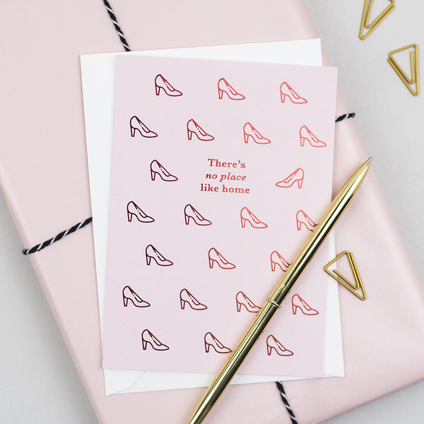 A new home card inspired by the Wizard of Oz and the iconic ruby slippers. It'a a pink card printed with red foil 'there's no place like home'