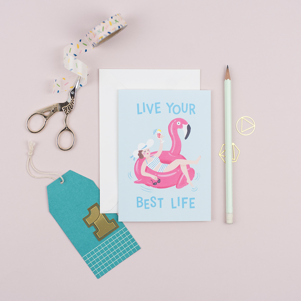 A birthday card that features an illustration of a woman holding a cocktail lounging on a flamingo pool float with a greeting that reads 'Live Your Best Life'