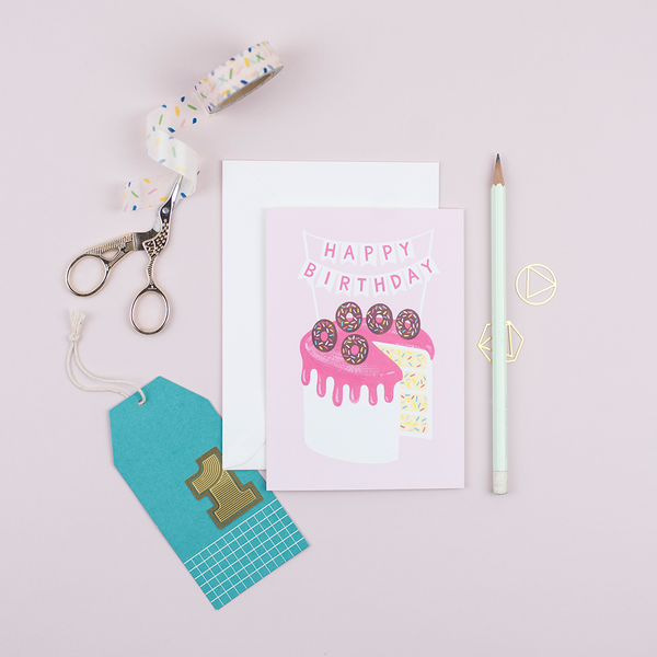 A birthday card featuring a hand-painted birthday cake with doughnuts and confetti sponge