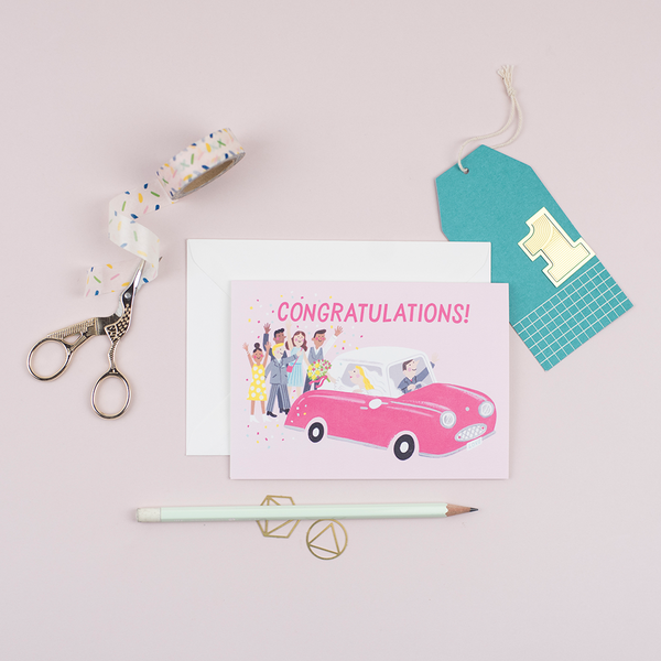 A wedding card that features a pink Nissan Figaro with a happy couple being congratulated by onlookers printed on a pink background