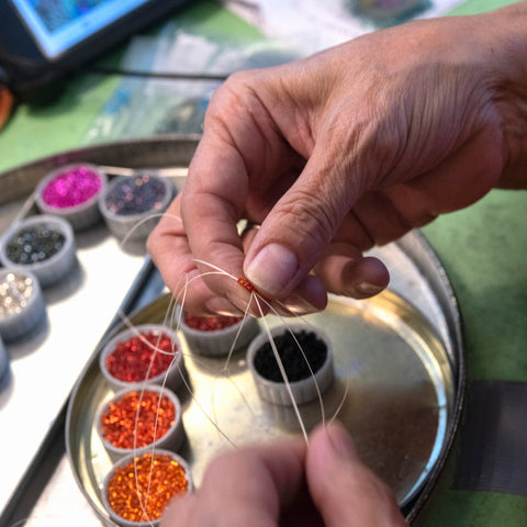A photograph of two hands stringing an array of tiny, colorful beads onto fishing line.