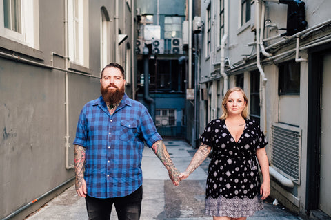 A couple standing standing side by side in a alley facing forwards and holding hands.  They are heavily tattooed and have cheeky grins on their faces.