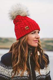 Woman wearing a navy colored unisex style Braided Knit Acrylic Toque that a real fur pom can be added to.