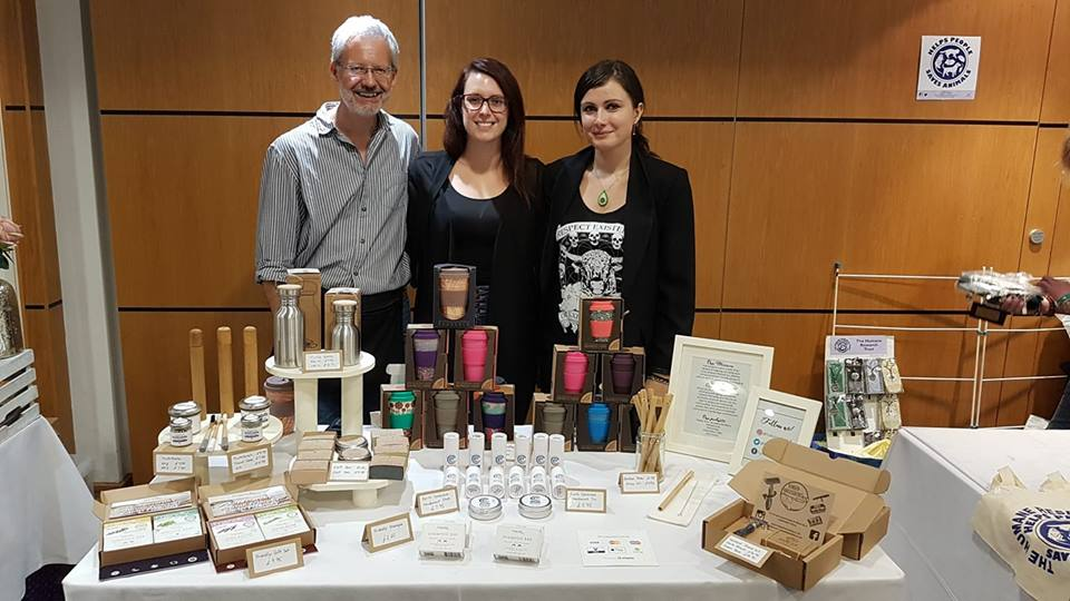 This picture shows the Full Circle Team: Paul, Emma and Johanna at their first event in Ipswich Vegan Market. They are standing behind a white table where reusable cups, plastic-free toothpaste, reusable bottles, safety razors and bamboo toothbrushes are displayed