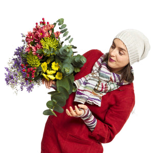 Woman wearing knitted sonet scarf and matching wristwarmers holding bouquet of flowers