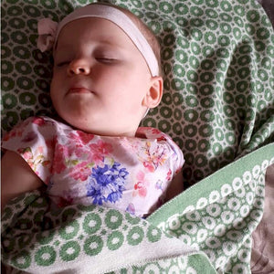 Baby girl wrapped in McKernan Baby Blanket Bubbles Green Earth