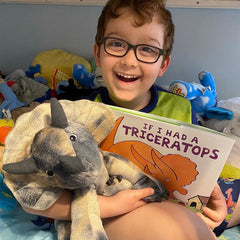 Boy Smiling with his Triceratops Book and Bear Box