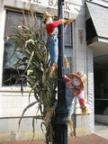 Two Scarecrows Climbing A Lamp Post