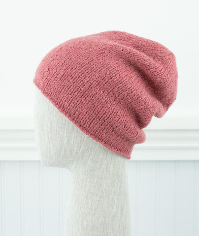 Dusty Pink slouchy hat on head form facing away to the left of camera.