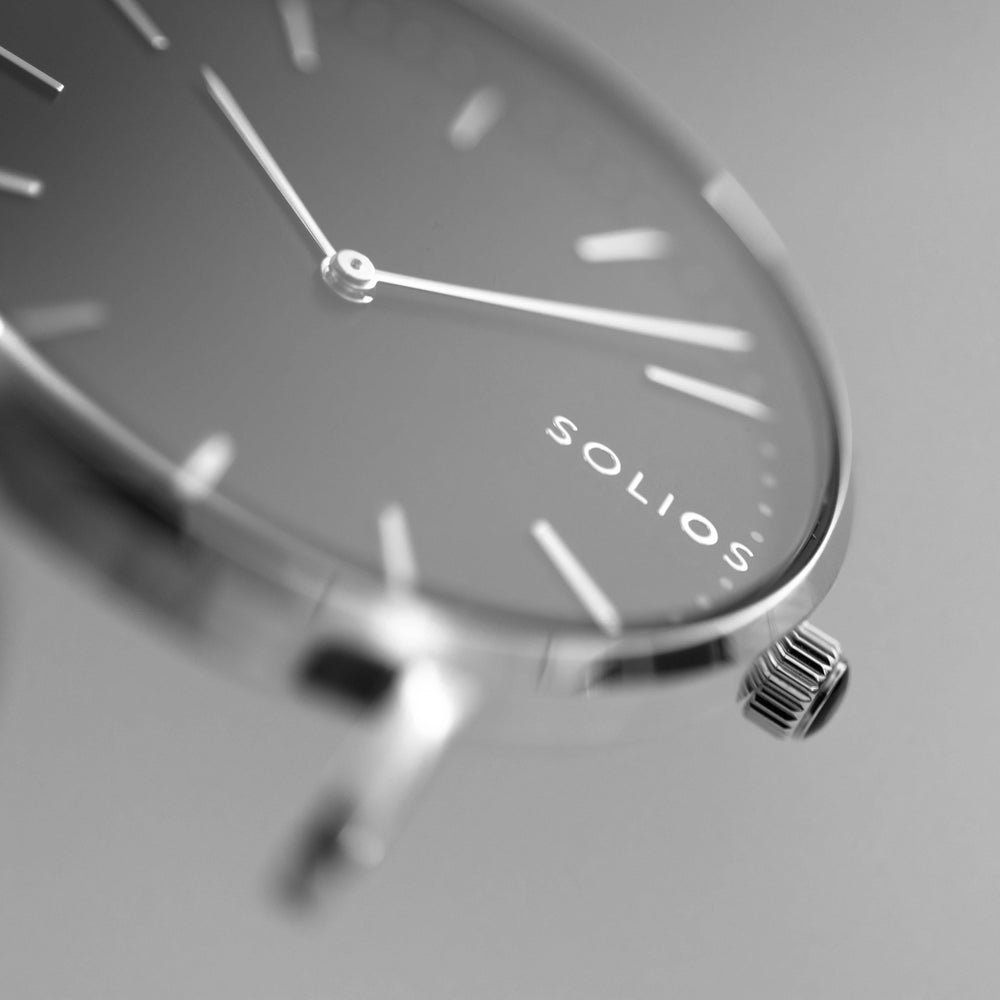 Elegant Solios logo on a minimal black dial and silver slim case.