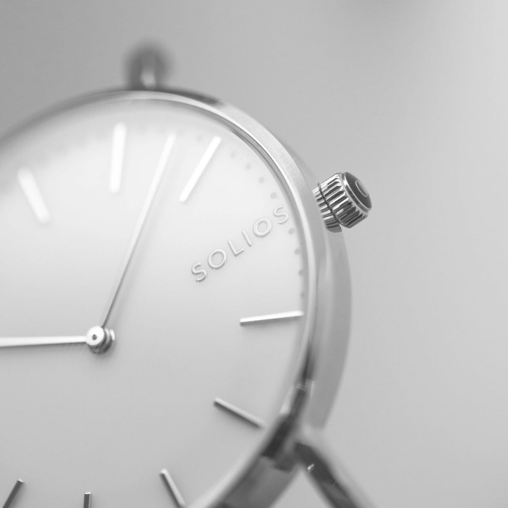 Elegant Solios logo on a minimal white dial and silver slim case.