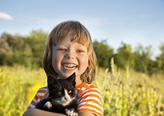 Happy child holding kitten|