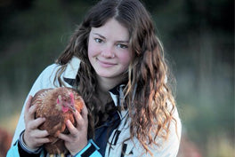 young woman holding an isa brown chicken