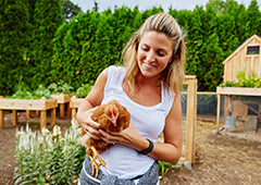 woman holding chicken in backyard