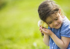 Young girl hugging baby chicken
